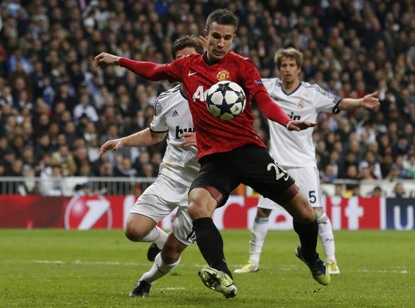 Robin Van Persie realiza un disparo ante la defensa del Real Madrid. AFP / END