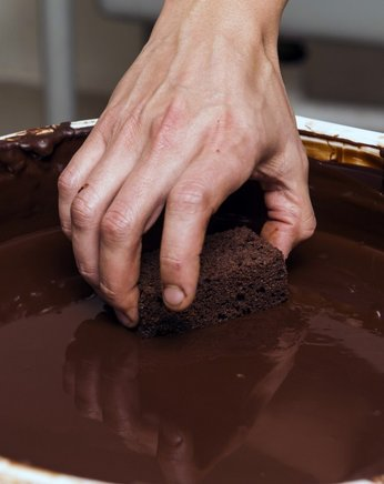Un brownie es cubierto con chocolate líquido. AFP / END