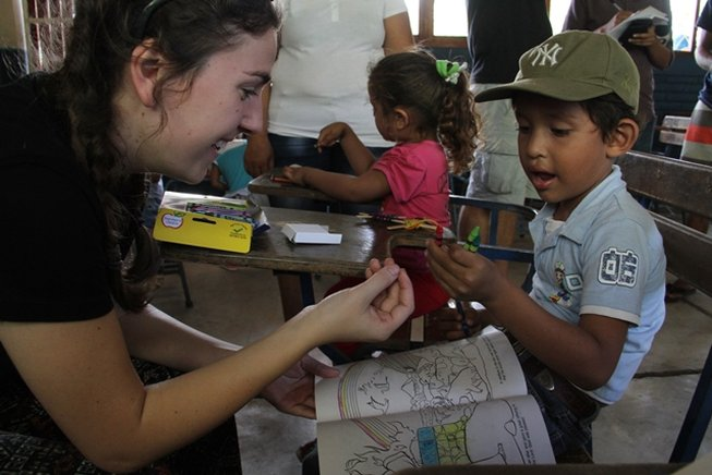 Voluntarios comparten libros y lápices para colorear con los niños. Lisandro Roque / END