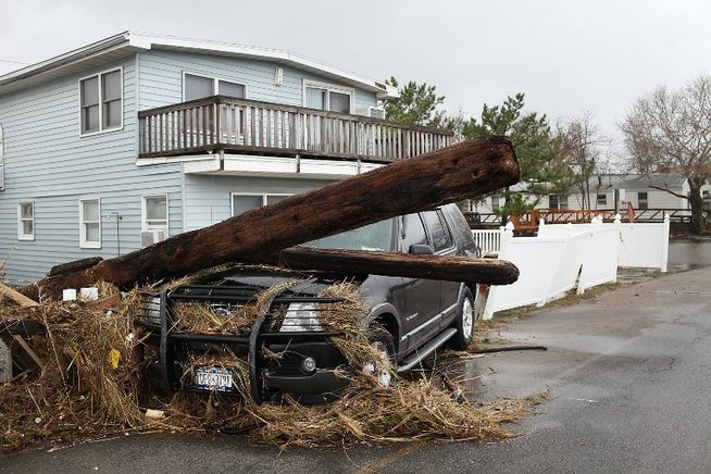 Un poste cayó sobre una camioneta tras ser derribado por los fuertes vientos y lluvias en el Barrio Breezy Point, Queens, en Nueva York. END/AFP/Spencer Platt/Getty Images