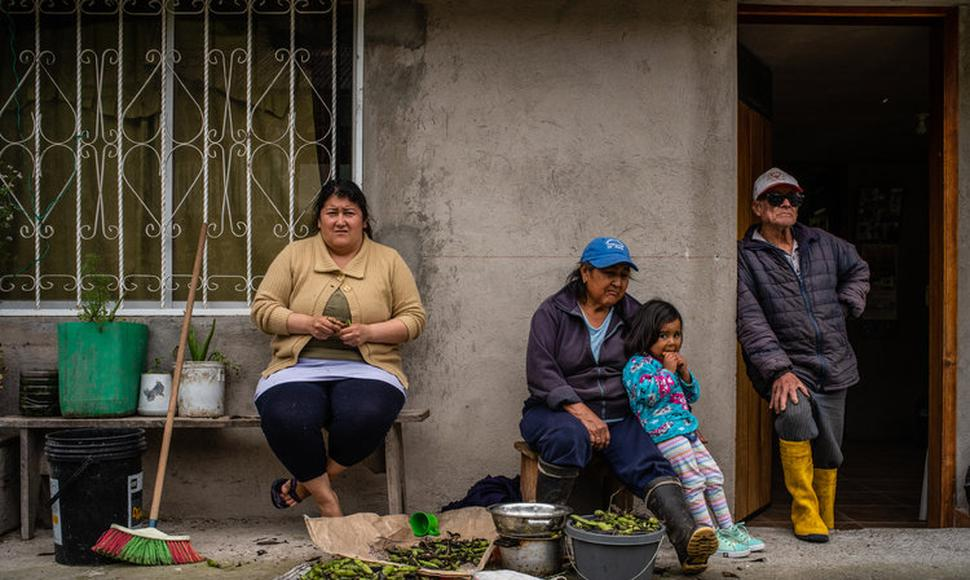 A family peeling beans at their house in the town of Cuyuja. They pay about $60 a month for electricity. (Federico Rios Escobar for The New York Tim