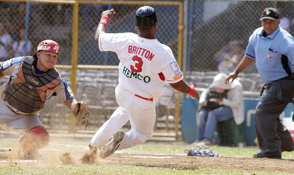 Winston Dávila intenta poner out a Dwight Britton en el plato.